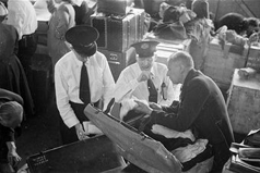 1950: Ellis Island immigration officers check the luggage of passengers from the last European displaced persons boat. (Credit: Ernst Haas/Getty Images)