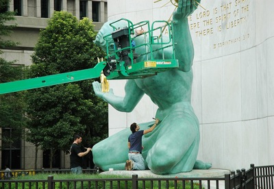 Workers cleaning up a statue by Marshall Fredericks titled 'The Spirit of Detroit.'